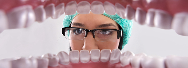 Female dentist over open patient's mouth looking in teeth